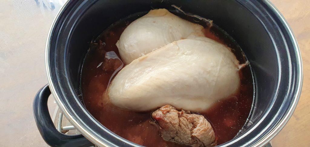 Hähnchenfleisch und Rindfleisch im Kochtopf per Sonnenstrahlen gekocht